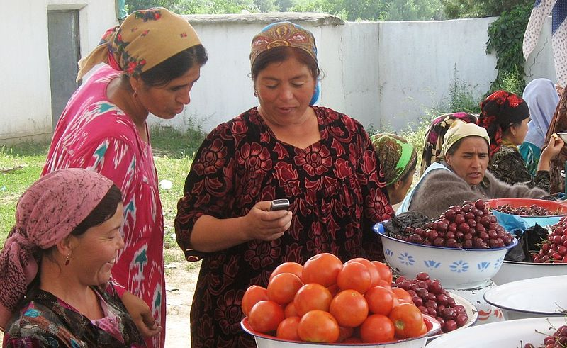 Woman uses cell phone at the market - Tajikistan. By Kate Dixon.